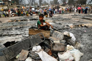 Cox's Bazar, Bangladesh. A young boy sits on a pile of burned items after a fire destroyed thousands of shelters in the Rohingya refugee camp