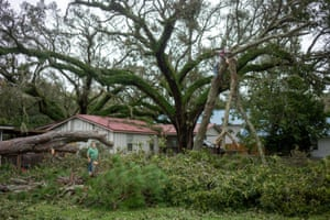 Tony Beritiech, of Dauphin Island, watches as his son Matt Beritiech, of Ocean Springs, cleans up a downed tree in front of Tony's house on Dauphin Island, Alabama.