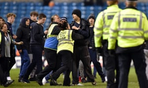 Millwall supporters are prevented from prolonging a pitch invasion at the end of their draw with Scunthorpe.