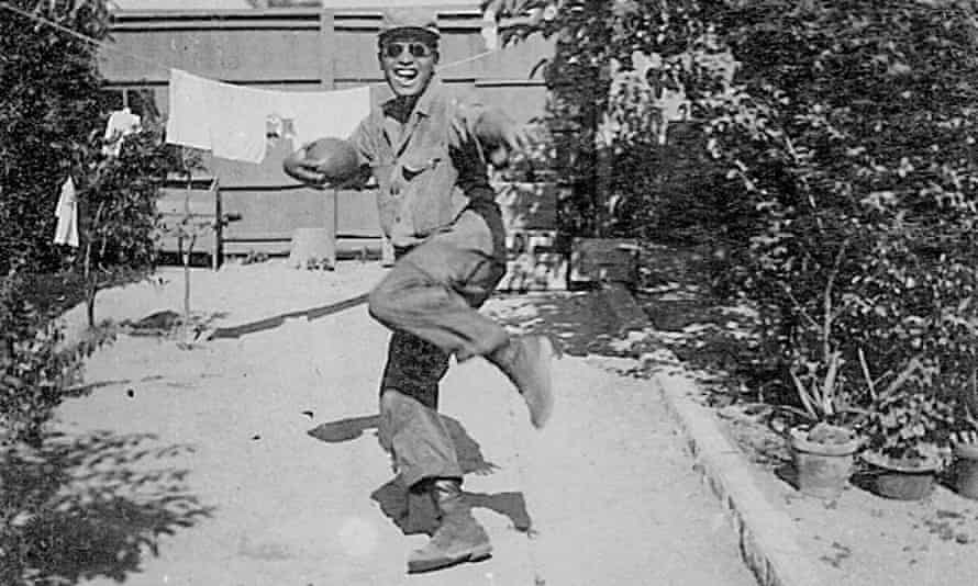 Horse Yoshinaga poses with a football during his army days