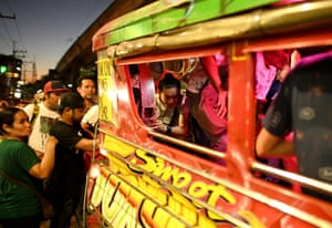 Commuters board a jeepney.