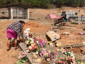 Floresmira Lopez rearranges flowers on her father's grave