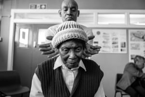 Michael gives Rose a neck a massage, from Windrush generation portraits by Jim Grover