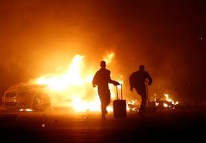 Ħal Far, Malta: People run past a burning vehicle during riots at a migrant camp