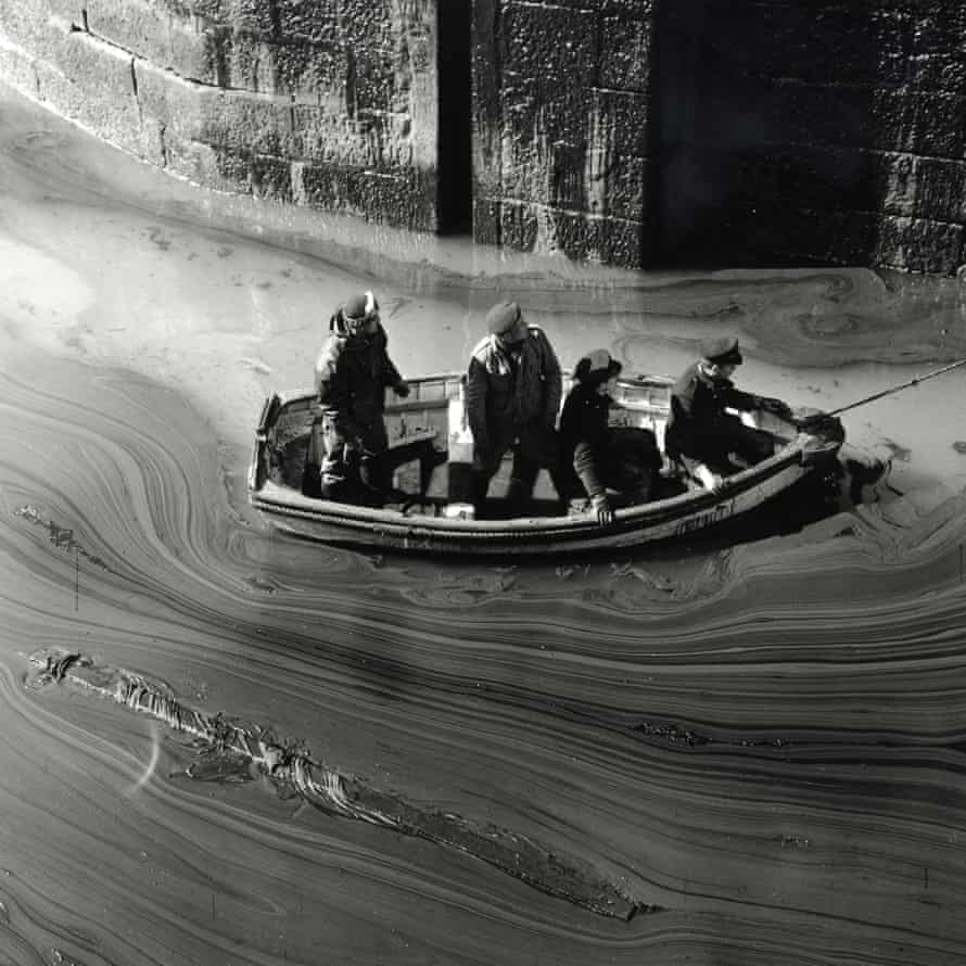Servicemen survey the oil slick in the harbour at Porthleven, Cornwall.