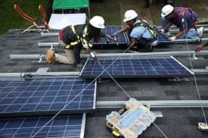 Workers install solar panels in Washington, DC. A boom in solar and wind power jobs in the US led a global increase in renewable energy employment.