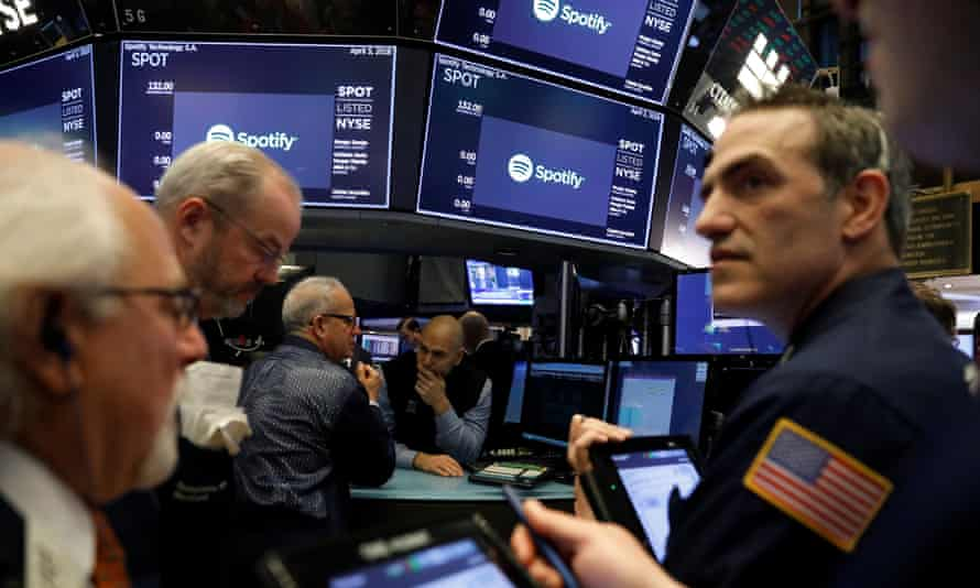 Traders await price updates of Spotify before the company's direct listing on the floor of the New York Stock Exchange on Tuesday.