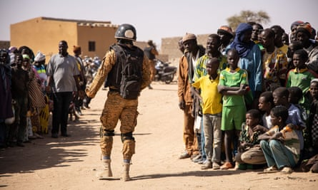 A government soldier on patrol in Dori next to refugees who had fled from attacks in northern Burkina Faso