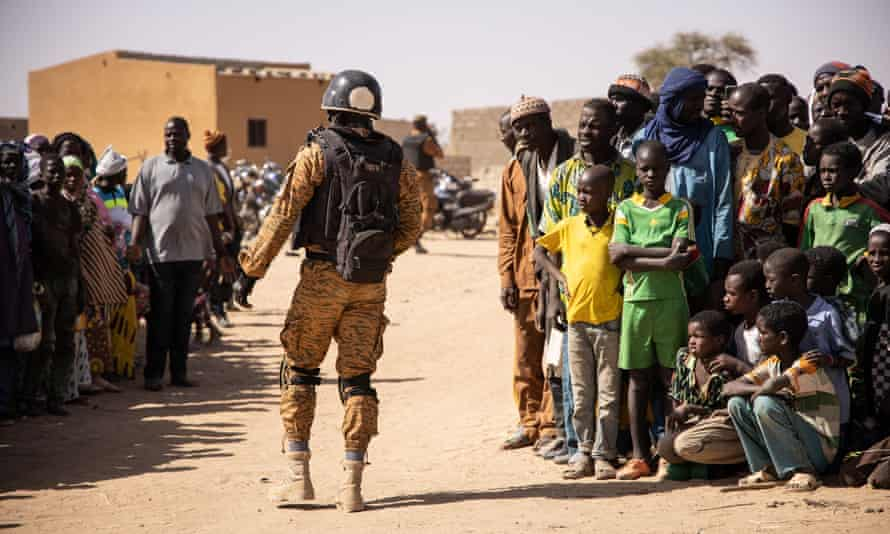 A Burkina Faso soldier patrols at a camp sheltering refugees from the fighting in Dori, in the north of the country.