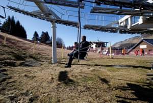 Boutx, France. Tourists sit on a chairlift at a ski slope closed due to lack of snow at Le Mourtis ski resort