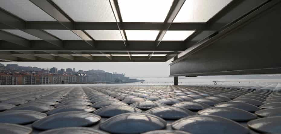 The view from under the gallery. The pearlescent discs adorning parts of the building resemble glittering barnacles.