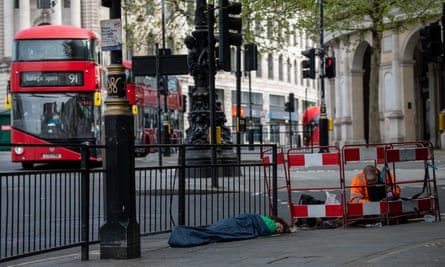 An electrician works on public services at Trafalgar Square, central London, while a homeless man sleeps next to him and buses go by