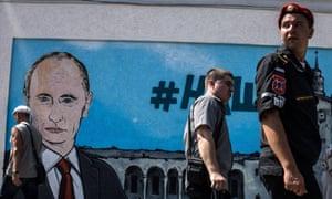 People walk by fresh graffiti depicting Vladimir Putin in Simferopol, Crimea. The real version will soon explore Byzantine-era wreckage in the Black Sea