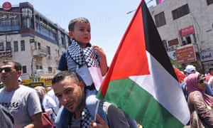 A Palestinian carries his son and a Palestinian flag in Ramallah, West Bank, during a protest in June.
