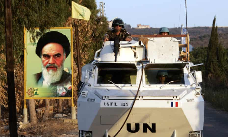 French UN peacekeepers pass a billboard showing Iran's late leader Ayatollah Khomeini following the Israel-Hezbollah war, southern Lebanon, September 2006