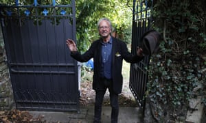 Austrian author Peter Handk greets the press outside his house in Chaville near Paris, on Thursday.