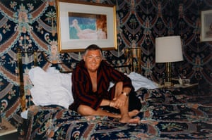 Grey-haired man in dressing gown sitting on a bed with a bedspread that matches the wallpaper