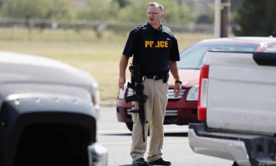 A police officer stands guard on E. 42nd Street in Odessa, Texas, on Saturday after the fatal shooting.