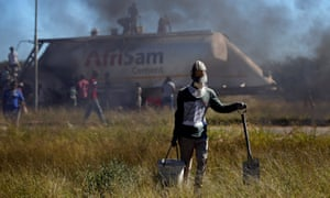 People loot cement from a truck during protests in Mahikeng, North West province.