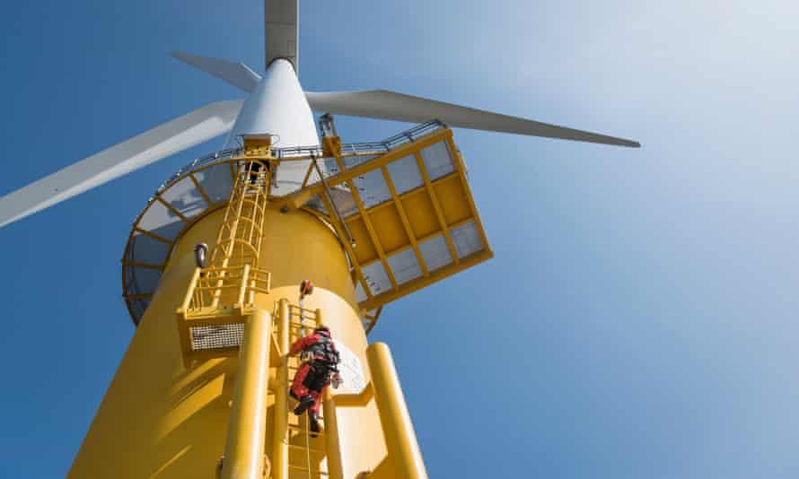 An engineer climbs a wind turbine.