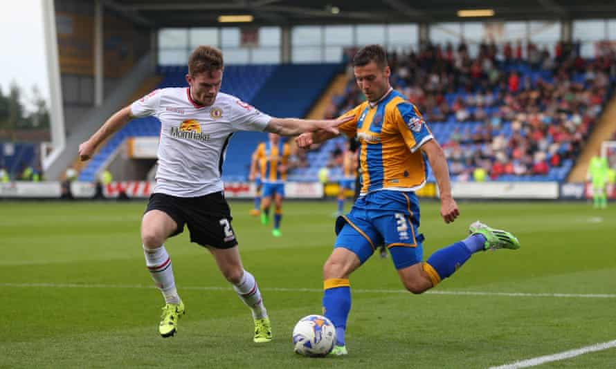 Mat Sadler of Shrewsbury Town attempts to pass the ball despite the efforts of Crewe Alexandra's Oliver Turton.