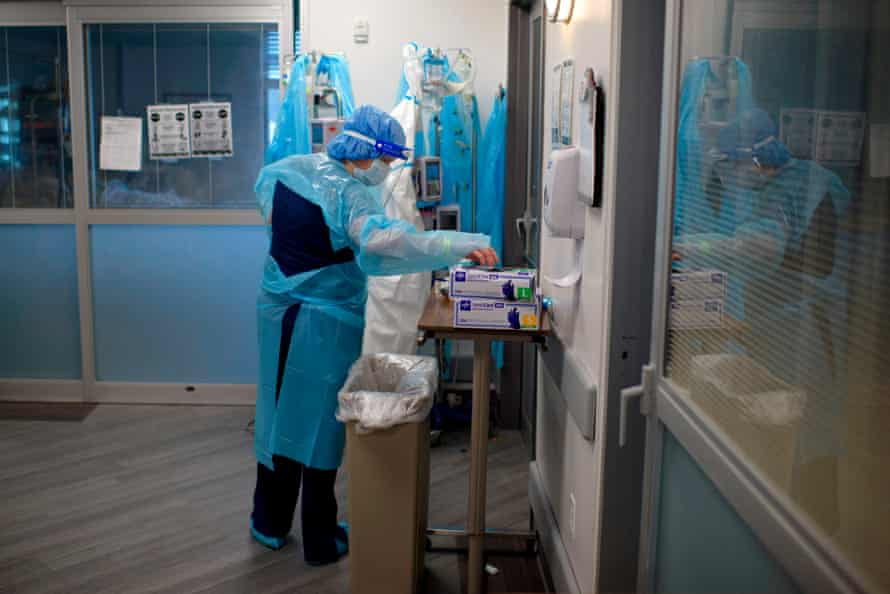 A healthcare worker puts on gloves in the ICU at Oakbend Medical Center in Richmond, Texas, on 15 July.