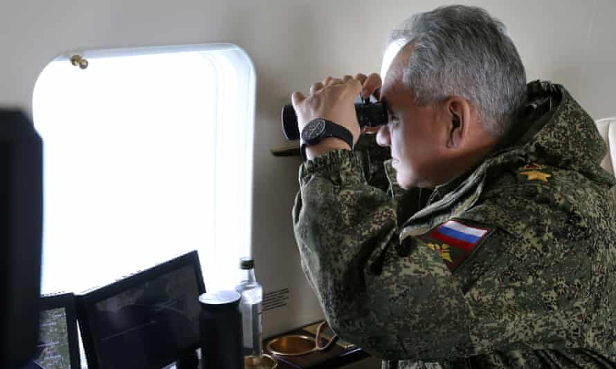 Russian defence minister, Sergei Shoigu, watches troops from onboard a military helicopter in Crimea.