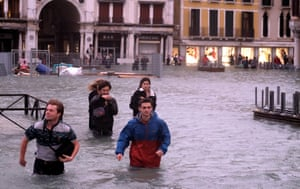 People walk in a flooded Saint Mark Square during a period of seasonal high water in Venice