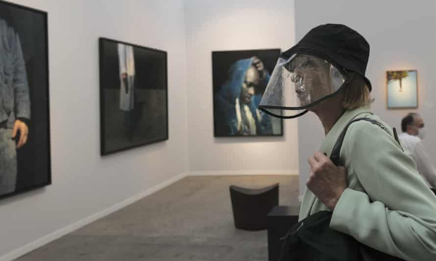 A visitor, wearing a protective face mask as a precaution against the coronavirus, looks on during the private view of Art Paris at the Grand Palais in Paris