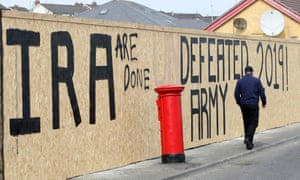 "A man walks past graffiti that has been amended to read ""IRA are done"" in the Creggan area of Derry in Northern Ireland on April 20, 2019 close to where Lyra McKee was shot."