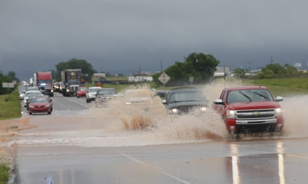 Vehicles drive through floodwater following heavy rains in El Reno, Oklahoma, on 21 May.