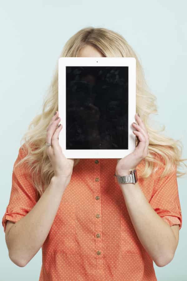 A women hides her face behind a tablet computer