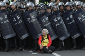 A woman sits in front of riot police blocking the road to protect protesters during an anti-government march on 24 April 2015 in Seoul, South Korea.