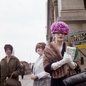 A woman in a fur coat, white gloves and an elaborate flower-shaped hat, looking towards the camera, with two other women in the background
