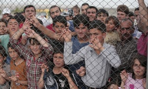 Refugees stand behind a wire fence
