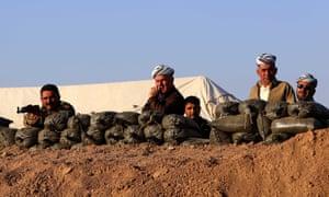 Iraqi Kurdish Peshmerga fighters take position behind sandbags on the front line in Khazer, 40 km West of Arbil, the capital of the autonomous Kurdish region of northern Iraq.