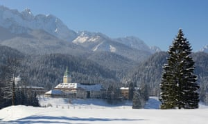 A snowy scene of Schloss Elmau Castle Hotel with forest and Wetterstein mountain range behind