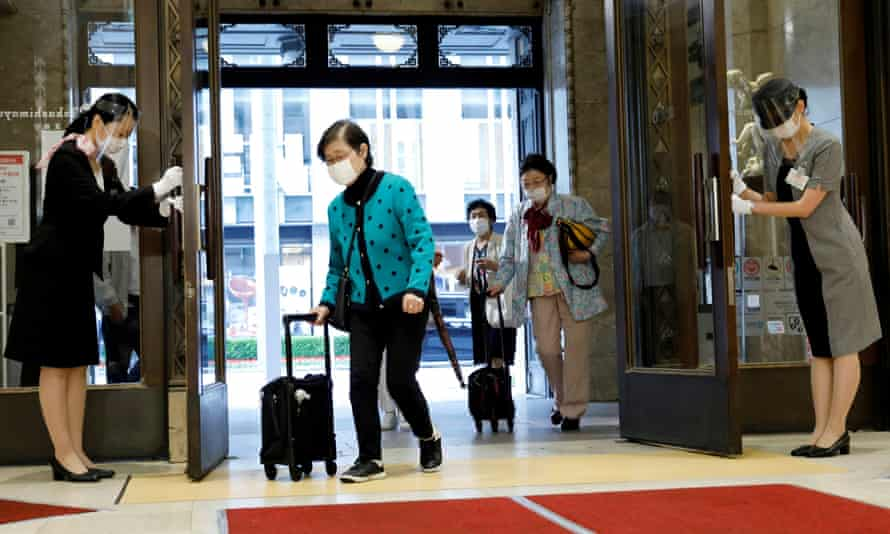 Staff members wearing face masks and shields bow to customers as the Nihombashi Takashimaya shopping centre partially reopens in Tokyo.