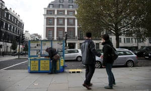 A woman cleans an information kiosk about Falun Gong outside the Chinese embassy in London