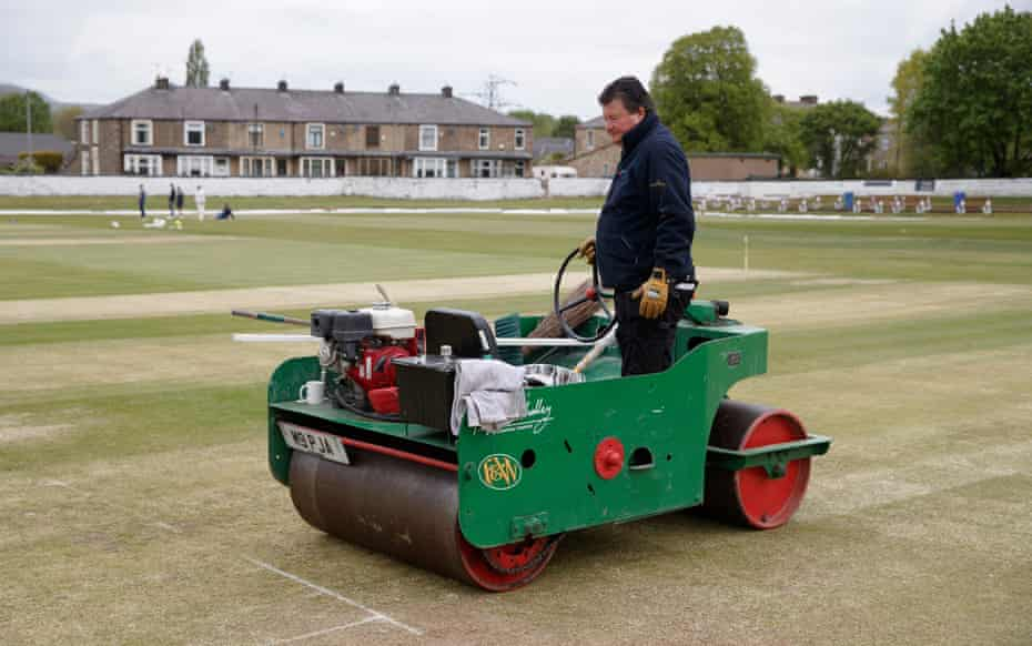 Stan Heaton, the chairman and groundsman of Lowerhouse, rolling the pitch before their Lancashire League match against Norden at the Brooks Foundation ground in Burnley.