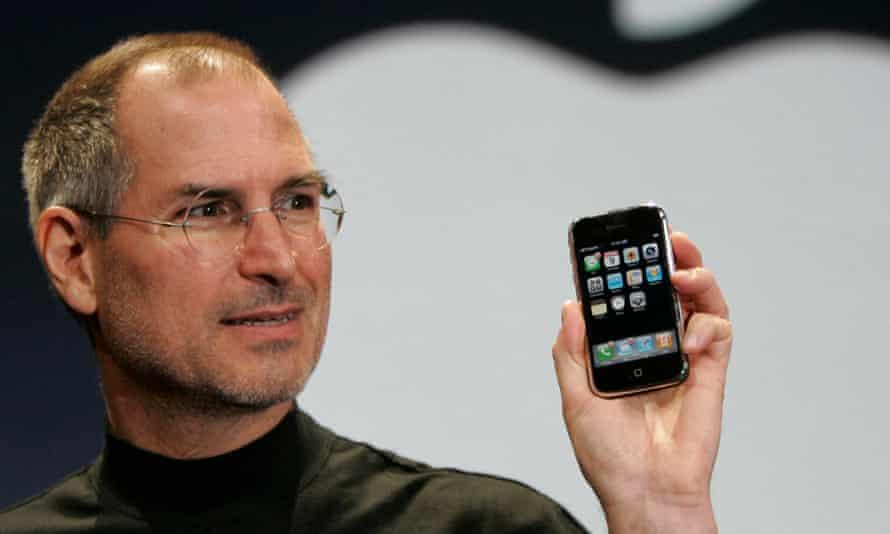Steve Jobs holds an iPhone