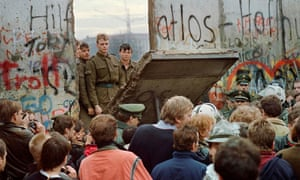 West Berliners crowd in front of the Berlin Wall in November 1989 as they watch East German border guards demolishing a section.