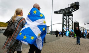 A man wrapped in a hybrid Scottish and EU flag