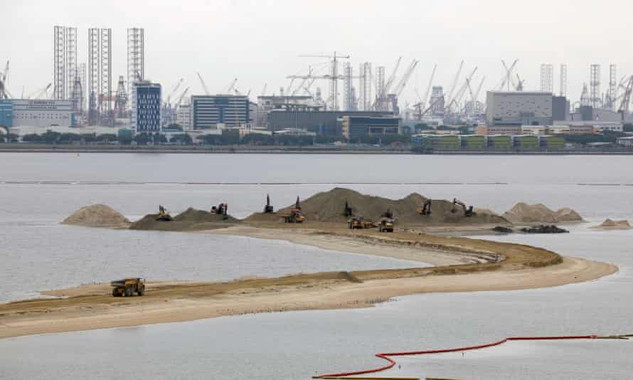 Trucks carry sand at the Forest City development in Johor Bahru, Malaysia