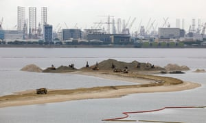 Trucks carry sand at land reclamation area overlooking Singapore's Tuas industrial area in the Country Gardens' Forest City development in Johor Bahru, Malaysia.