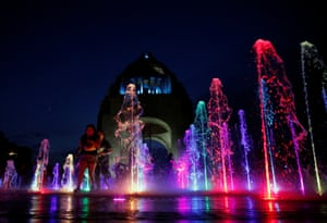 People run through an illuminated fountain at the Monument of the Revolution, Mexico City, Mexico