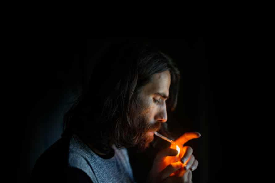 Behrouz Boochani lights on his hand-rolled cigarette.