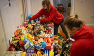 Staff organise donations for vulnerable families at a food bank.