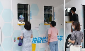 Medical workers swab throat of people for nucleic acid testing of Covid-19 at a testing site amid the coronavirus outbreak on 28 June 2020 in Beijing, China.