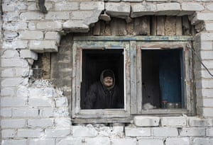 An elderly woman looks through the window in her house damaged by shelling in Avdiivka, eastern Ukraine